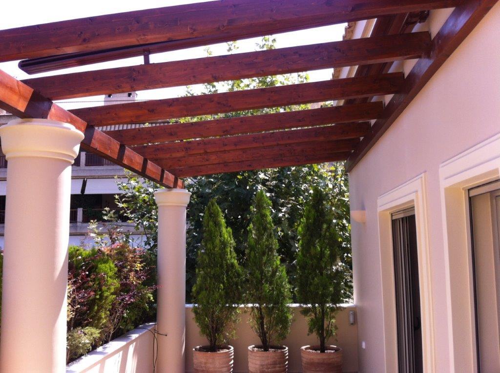 Ξύλινη πέργκολα με δοκούς και σταθερές μόνιμες διακοσμητικές σανίδες στο πάνω μέρος